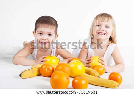 Cute baby girl and baby boy play with fruits over white - stock photo