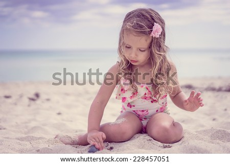 Cute baby girl at the beach - stock photo