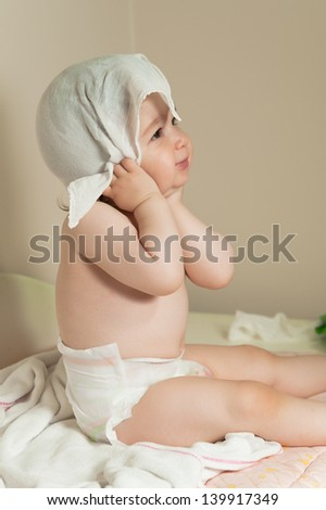 Cute baby girl being dried her hair oneself with lawn after shower - stock photo
