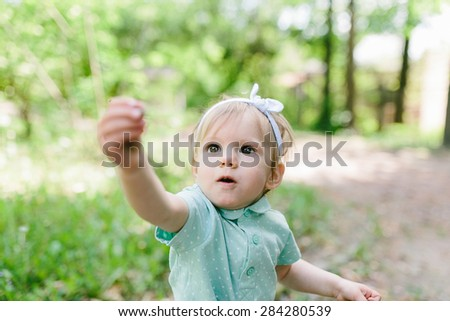 cute baby girl blowing a white dandelion seeds in her hands