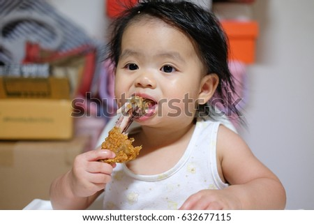 Cute baby girl ,close-up  little asian girl eating fried chicken