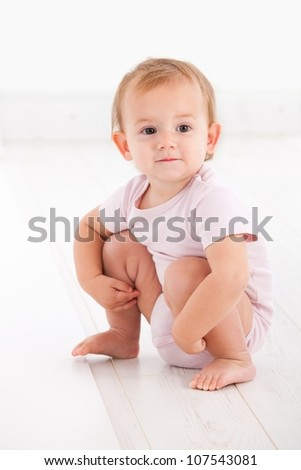 Cute baby girl crouching on floor in pink short sleeve bodysuit. - stock photo