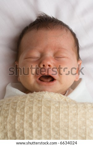 Cute baby girl crying under a blanket