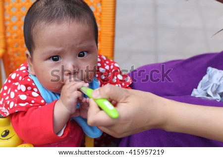 Cute baby girl eating first food, trying to hold the spoon and feed herself - stock photo