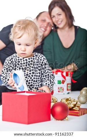 Cute baby girl getting ready for her first christmas with her parents. - stock photo
