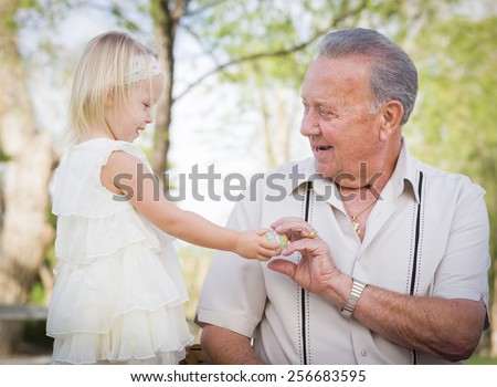 Cute Baby Girl Handing Easter Egg to Grandfather Outside at the Park. - stock photo