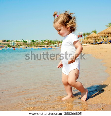 Cute baby girl having fun on tropical beach. Summer vacation concept. - stock photo