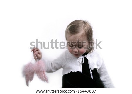 Cute baby girl holding angel wings - stock photo