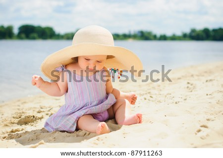 cute baby girl in a beige hat sitting and playing on the beach with sand. - stock photo