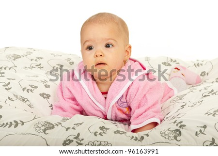 Cute baby girl in bathrobe crawling in bed against white background - stock photo