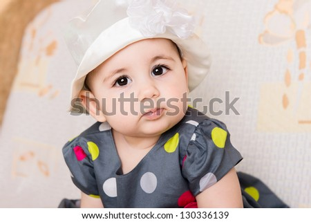 Cute baby girl in dotted dress in elegant hat