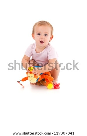 Cute baby girl in pink bodysuit playing with soft toy, squatting on floor. - stock photo