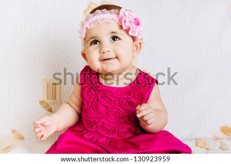 Cute baby girl in pink floral dress - stock photo