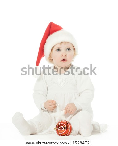 Cute baby girl in Santa's hat playing on the floor