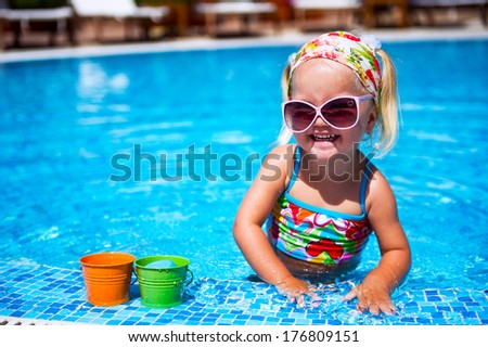 Cute baby girl in sunglasses playing with toys in the swimming pool outdoors - stock photo