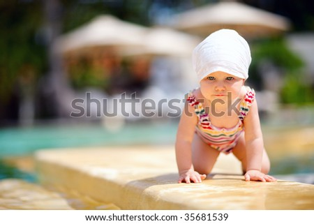 Cute baby girl in swimsuit relaxing by the pool - stock photo
