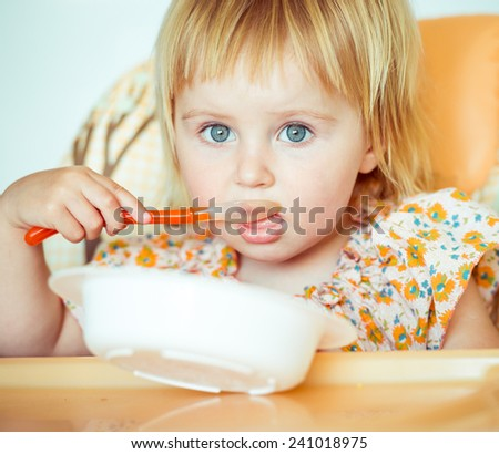 cute baby girl is holding a spoon and going to eat - stock photo