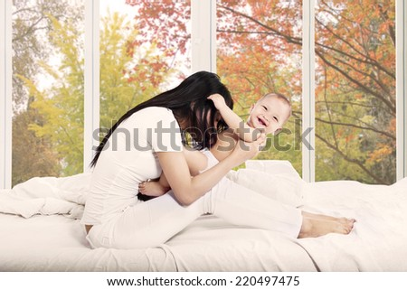 Cute baby girl laughing with her mother on bedroom at home in autumn - stock photo