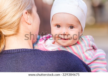Cute baby girl looking out from mother's back on mother's hands - stock photo