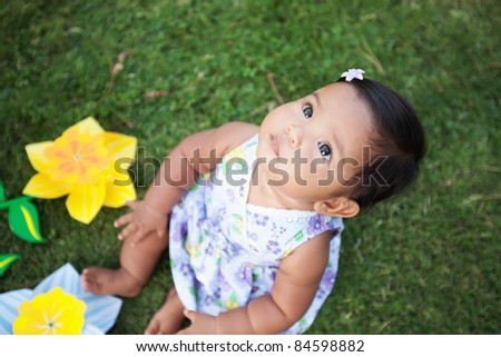 Cute baby girl looking up at the sky sitting on the lawn with pi - stock photo