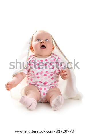 Cute baby girl looking up in excitement sitting under white blanket isolated on white background with shadow