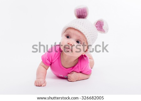 cute baby girl lying in a bright red T-shirt on a white background wearing a hat in the form of a Christmas bunny with pink ears and tail, with depth of field Photo - stock photo
