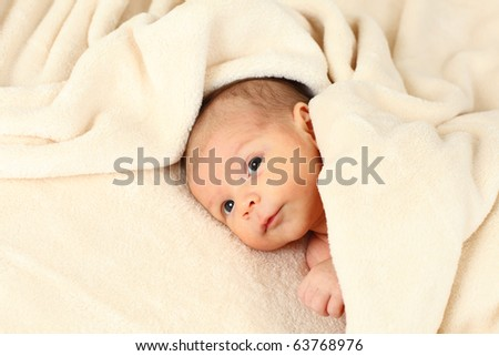 Cute baby girl lying in a soft blanket - stock photo