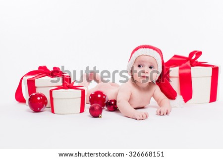 Cute baby girl lying naked on her stomach on a white background in a red New Year's cap among red Christmas balls and red boxes with gifts, picture with depth of field - stock photo