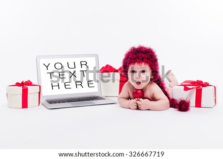 Cute baby girl lying naked on her stomach on a white background next to a laptop in a red New Year's cap among red Christmas balls and red boxes with gifts picture with depth of field - stock photo