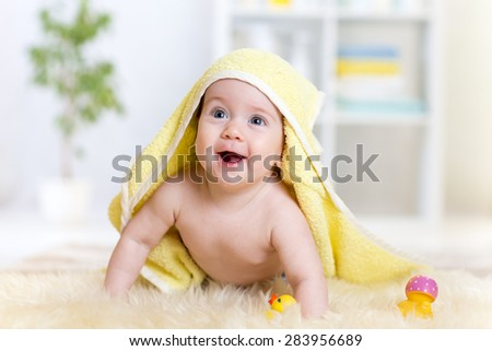 Cute baby girl lying on fur bed while smiling on camera under towel - stock photo
