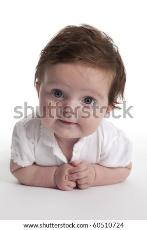 Cute baby girl lying on her belly on white background - stock photo