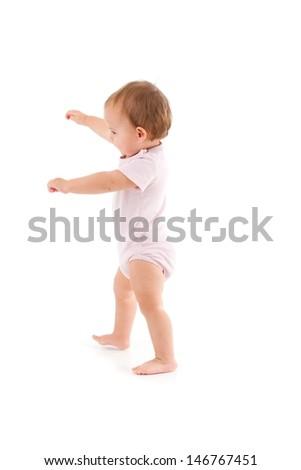 Cute baby girl making first steps, balancing. - stock photo