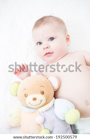 Cute baby girl playing on a white blanket.