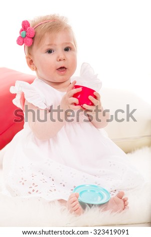 Cute baby girl playing with a cup of tea toy home - stock photo