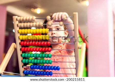 Cute baby girl playing with abachus - stock photo