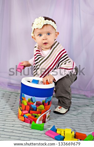 Cute baby girl playing with developmental toy - stock photo