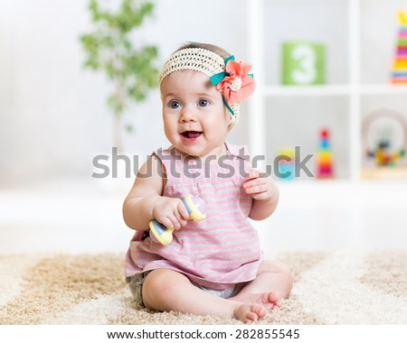 cute baby girl playing with toy indoors - stock photo