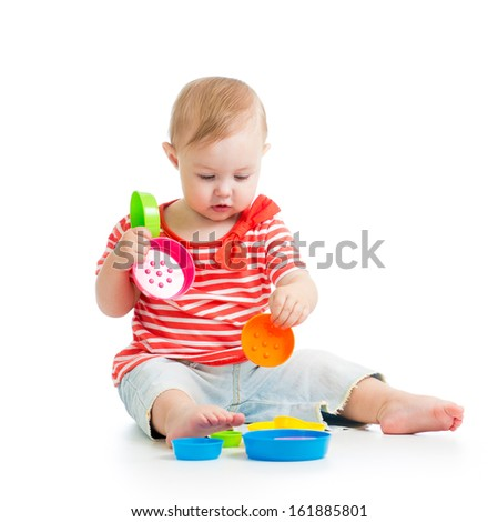 Cute baby girl playing with toys while sitting on floor, isolated over white