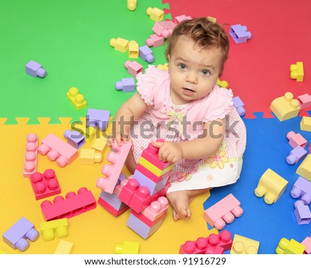 Cute baby girl plays with multicolored blocks toy - stock photo