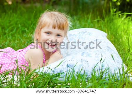 Cute baby girl resting on soft pillow in fresh spring grass - stock photo