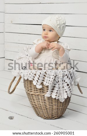 Cute baby girl sitting in a basket in a knitted hat. - stock photo