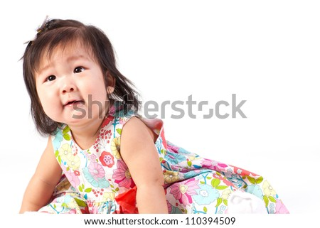Cute baby girl sitting in studio and look up isolated on white