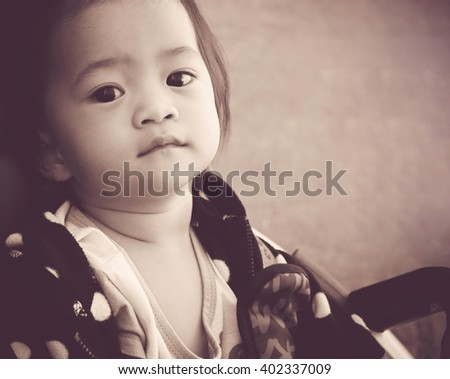 Cute baby girl sitting in the buggy with vintage style - stock photo