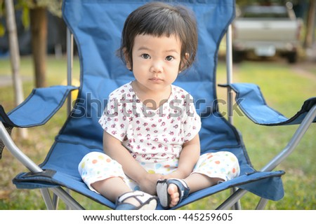 Cute baby girl sitting on a small picnic chair in a garden