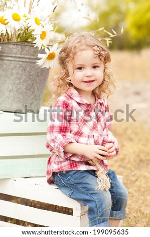 Cute baby girl sitting on crates with decorations outdoors - stock photo