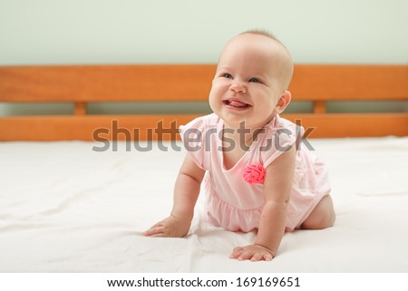 Cute baby girl sitting on the white bedding and smiling - stock photo