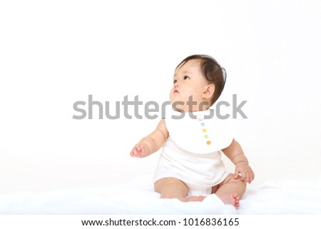 Cute baby girl sitting on white background