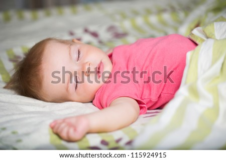 Cute baby girl sleeping laying on a white - green blanket. - stock photo