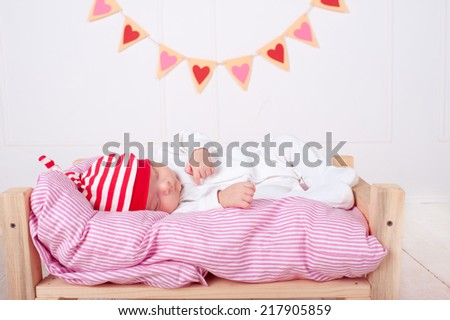 Cute baby girl sleeping on soft bed with hearts on background. Valentines decorations.  - stock photo