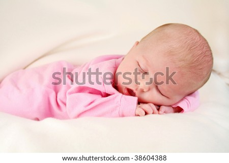 Cute baby girl sleeping with her hands under her face, laying on a white blanket.